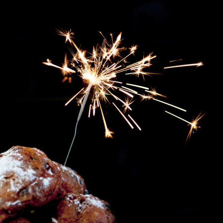 a pile with oliebollen with fireworks on a white background Stock Photo
