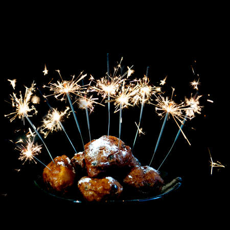 a pile with oliebollen with fireworks on a plate on a white background Stock Photo