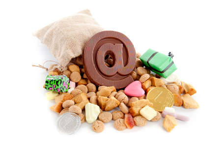 gingernuts: a jute bag full of pepernoten, a atpersand made of chocolate and a lot of candies on a white background
