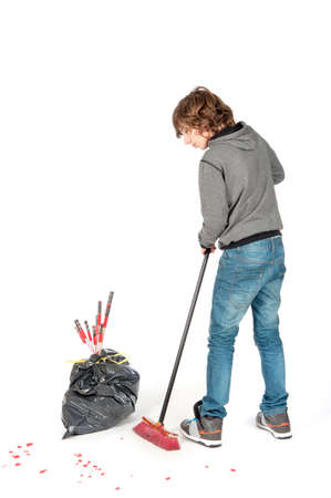 a teenage boy with a broom, cleaning the mess on new years day photo