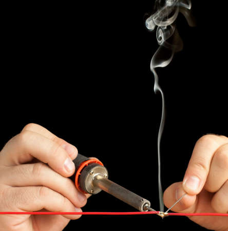 electronic background: Technician Soldering a Red Wire on a Pure Black Background.