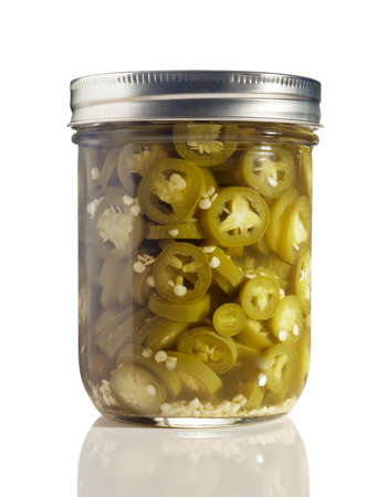 Sliced Jalapenos (Capsicum Annuum) in a Glass Jar on White 写真素材