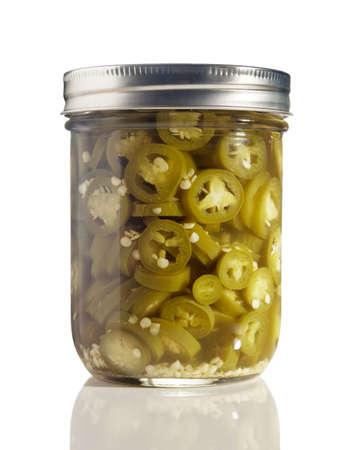 sottoli: Jalapenos a fette (Capsicum annuum) in un vaso di vetro su bianco