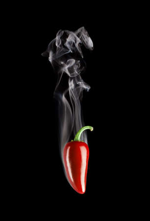 Smoking hot red jalapeno pepper (Capsicum Annuum) isolated on a pure black background.