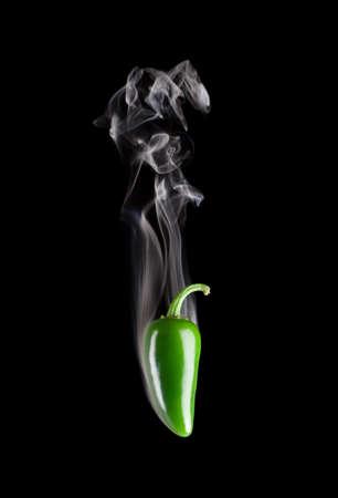 pepe nero: Fumo peperoncino verde jalapeno (Capsicum annuum) isolato su uno sfondo nero puro.