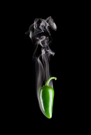 Smoking hot green jalapeno pepper (Capsicum Annuum) isolated on a pure black background. photo