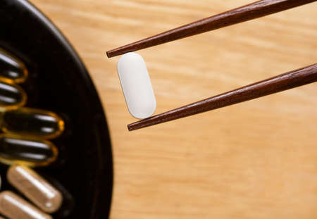 Someone using chopsticks to take supplements.