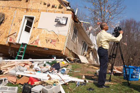 LAPEER COUNTY, MI - MARCH 16  WNEM News reporter James Felton videotapes the aftermath of a home heavily damaged by an F2 tornado that swept through Oregon Twp in Lapeer County, MI on March 15, 2012  Stock Photo - 12926373