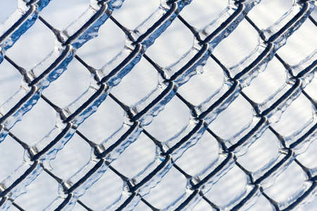 Ice covered chain link fence from a severe ice storm  Stock Photo