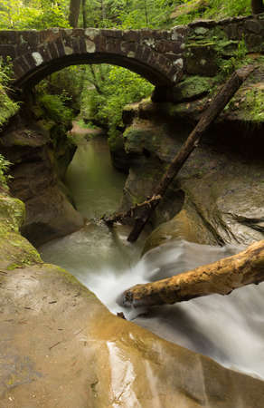 Tranquil stream flowing under a stone bridge at Hocking Hills State Park, Ohio.