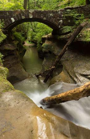 natural bridge state park: Tranquil stream flowing under a stone bridge at Hocking Hills State Park, Ohio.