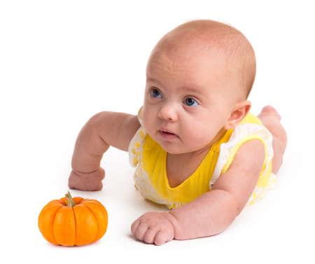 Baby meisje met een kleine pompoen geïsoleerd op een witte achtergrond