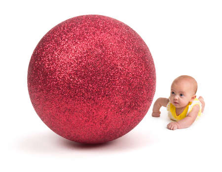 Cute Baby looking at a Huge Christmas Ornament on white 写真素材