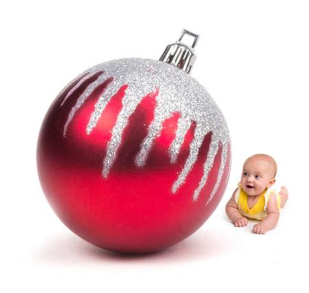 Leuke Baby die bij een Reusachtig Ornament van Kerstmis op wit glimlacht