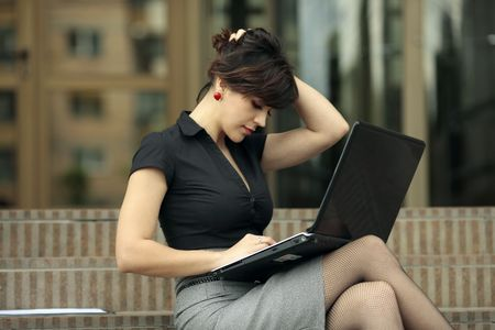 university life: busy young attractive lady playing with her hair and looking at a laptop on the stairs in front of an office building