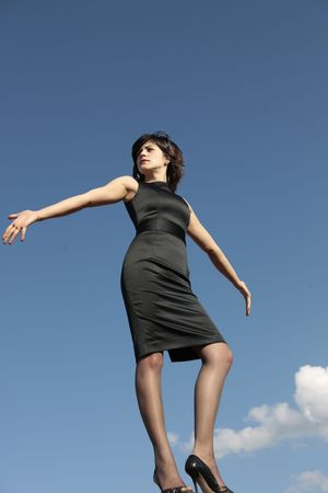 young business woman with her hands spread out and looking up from the top of the world with the sky as a background  Stock Photo
