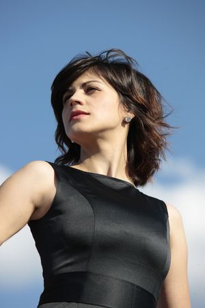 close up of young business woman looking up from the top of the world with the sky as a background