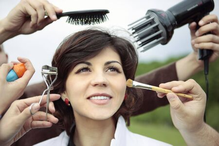 young smiling lady surrounded by hands that are working at her face and hair Stock Photo - 3278959