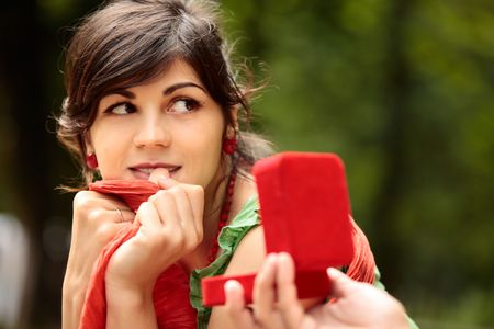 Young beautiful lady looking at the someone who is holding in front of her a red opened gift box