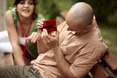 Playful man opening slowly a red ring box making a young lady to be very curios whats inside photo