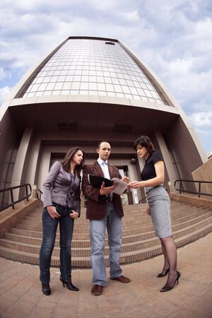 a fish eye look with business team talking outdoors in front of a sky high building Stock Photo - 3278955