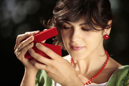 beautiful lady Peeking at an opened red jewelry box outdoors