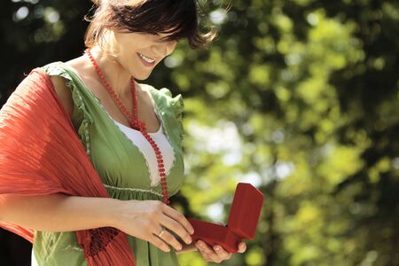 young happy woman smiling outdoors with a jewelry box in her hands Stock Photo