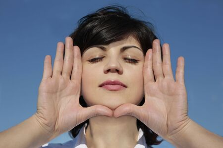 eyesclosed: young attractive girl with her hands as a frame around her face outdoors Stock Photo