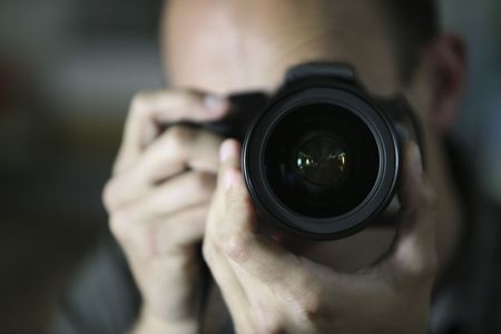 man holding a camera looking at the camera, front view