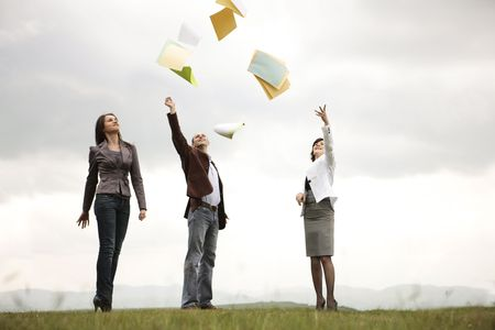 Young team shouting their victory to the world by trowing documents paper in the air outdoors Stock Photo