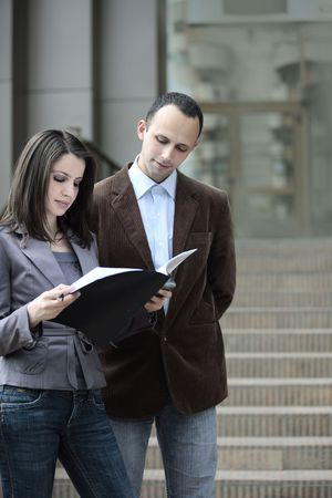 client looking at a contract outdoors next to a business man Stock Photo