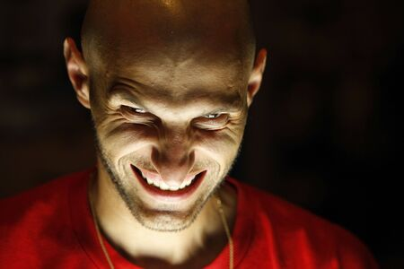 terrifying man with a grin as a smile looking at the camera with his chin down and the light under his face photo