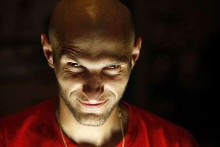 terrifying man with a smirk as a smile looking at the camera with his chin down and lighted from under his chin up Stock Photo - 3309837