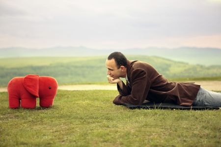 business man laid down talking with a toy elephant on green grass