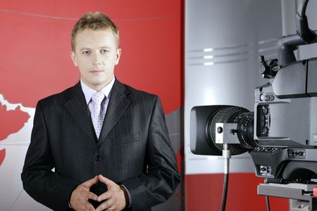 news reporter: news presenter in TV studio in front of video camera