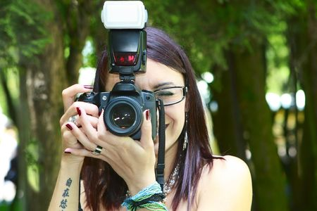 short focal depth: beautiful photographer holding a camera and looking at the camera