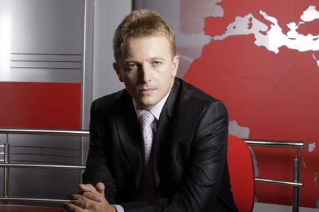 Ernstige verslaggever in televisie-studio te kijken naar de camera