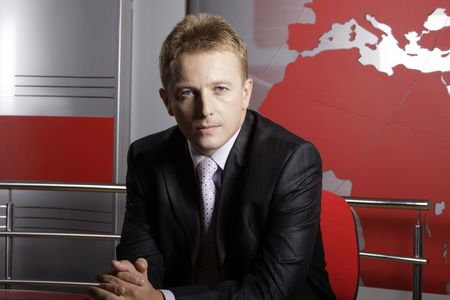 Serious reporter in television studio looking at the camera