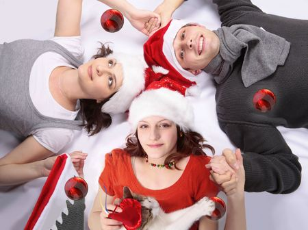 Teenager girl holding mother and fathers hands in a circle with Christmas hats and cat playing photo