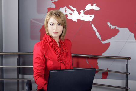 beautiful news television presenter in front of the laptop and looking at the camera