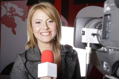 TV en vivo con la transmisión de un reportero sonriente delante de la cámara de video Foto de archivo