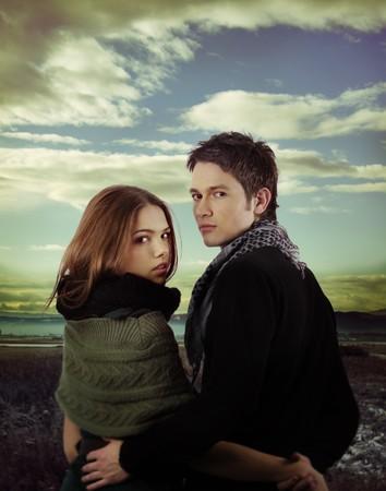 faire l amour: couple d'amoureux se tenant par la main et regardant la cam�ra en plein air contre le ciel dramatique