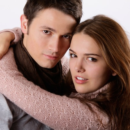 attractive couple holding each other and looking at the camera Stock Photo