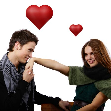 handsome boy kissing a beautiful girls hand with hears around Stock Photo