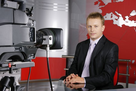 blond middle age news presenter in studio in front of the video camera Stock Photo