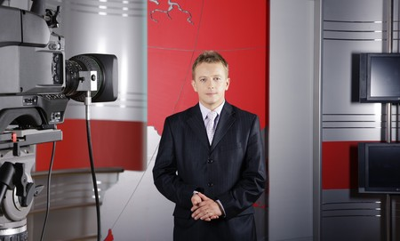 blond middle age news presenter in studio in front of the camera with braking news reports  Stock Photo