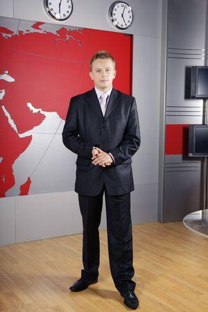 reportero: presentador de noticias de toda la longitud de pie delante de la c�mara en un estudio de televisi�n Foto de archivo