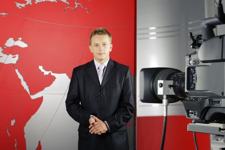 serious middle age attractive news reporter standing in front of the video camera in a television studio photo
