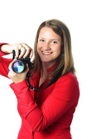 Young beautiful blond female photographer holding the photo camera. Isolated on white background Stock Photo