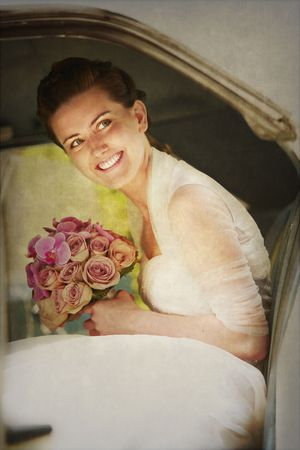 Happy smiling bride in a luxury white car with a bouquet of flowers in her hand